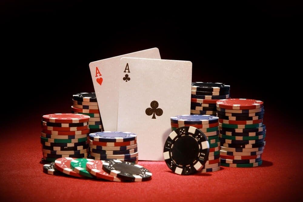Pokerchips mit Ass-Paar auf Pokertisch