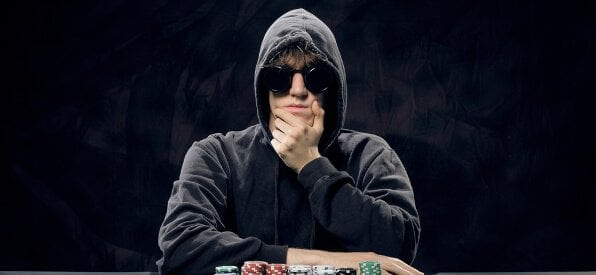 Pokerspieler mit Pokerface, Chips-Stapel und Ass-Paar